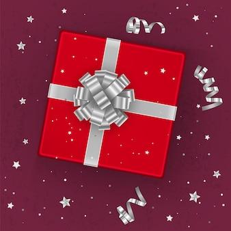 Uma caixa de presente vermelha realista decorada com um laço prateado, vista de cima.