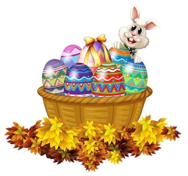 Uma cesta cheia de ovos de páscoa e um coelho