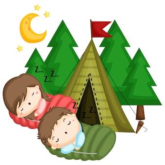 Uma criança dormindo em um saco de dormir fora de sua tenda