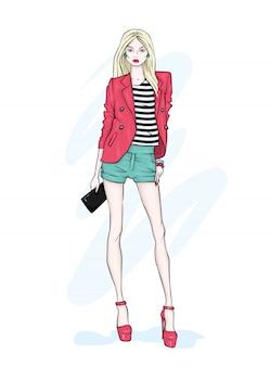 Uma garota alta e esguia de shorts, jaqueta e sapatos de salto alto.