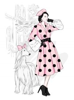 Uma garota alta e magra em casacos e botas com cachorro lindo.