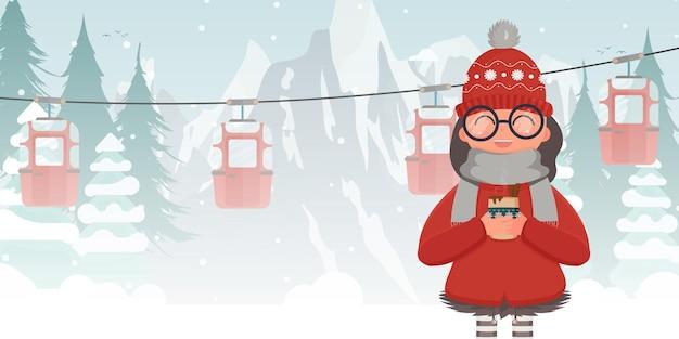 Uma garota com roupas de inverno está segurando uma bebida quente. teleférico ou funicular.