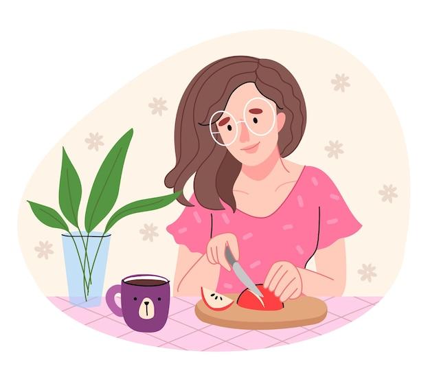 Uma garota com uma camisa rosa está cozinhando na cozinha. mulher de óculos redondos corta uma maçã.