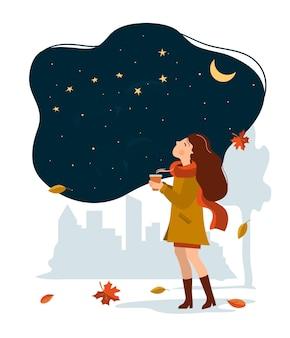 Uma garota com uma xícara de café caminha pelo parque outono e olha para o céu estrelado.