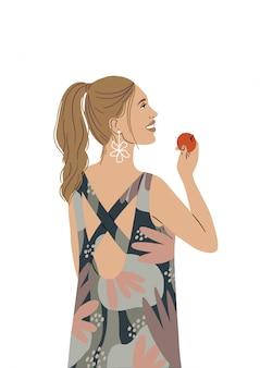 Uma garota linda em um vestido brilhante sorri e tem uma maçã na mão.