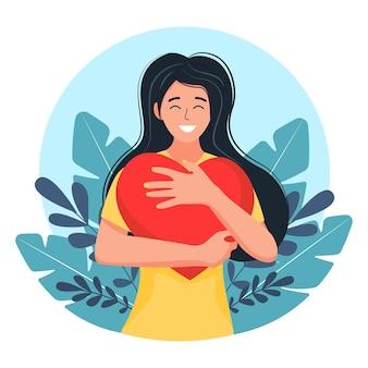 Uma jovem abraça um grande coração com amor e carinho. a garota tem um coração vermelho nas mãos. autocuidado e conceito de corpo positivo.