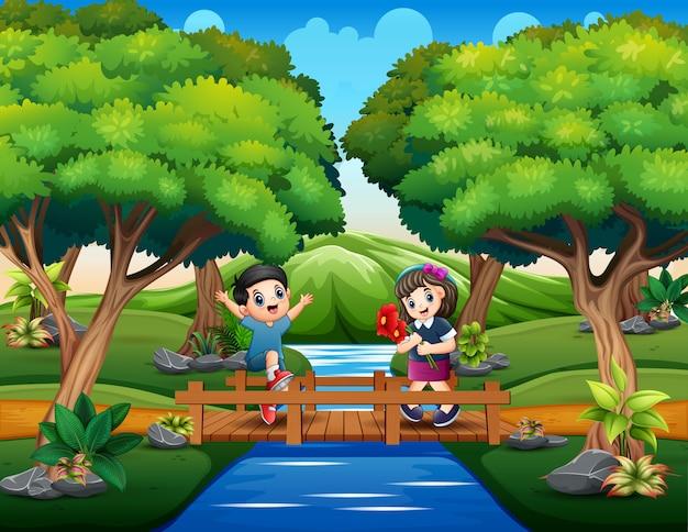Uma jovem garota e um jovem garoto na ponte de madeira