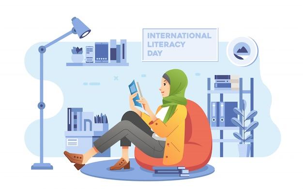 Uma jovem garota hijab sentada em um saco de feijão enquanto lê um livro na sala de estar com o interior da casa como pano de fundo