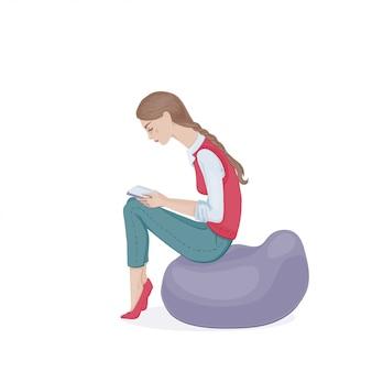 Uma jovem mulher com uma trança em um colete rosa e calça jeans, sentado em uma cadeira de pufe e lendo um livro. uma aluna.