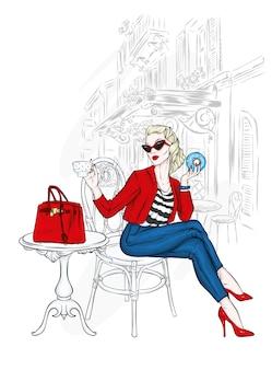 Uma linda garota de calça e jaqueta está sentada em um café.