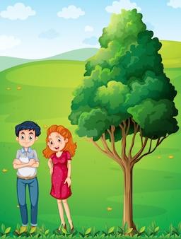 Uma mãe e um pai perto da grande árvore no topo da colina