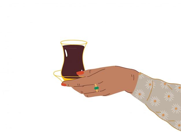 Uma mão feminina com uma bela manicure e jóias segura uma xícara de chá turco do azerbaijão. vista lateral das mãos segurando armudu. ilustração na moda em estilo cartoon. design plano.