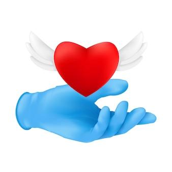 Uma mão humana usando luva cirúrgica protetora azul com um coração vermelho voador com asas de anjo.