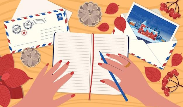 Uma mão que assina um cartão de natal. um conceito de envio de cartas, um cartão de felicitações para amigos. uma mesa com envelope postal com carta, caderno, viburnum, cones, poinsétia.