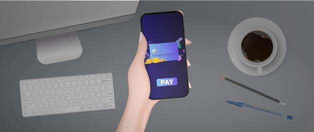 Uma mão segura um telefone com um aplicativo de pagamento. botão de pagamento.