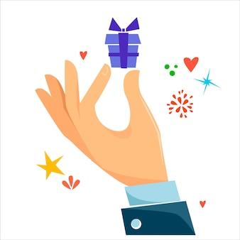 Uma mão segura uma caixa com um presente símbolos de estrelas e corações em torno do conceito de férias