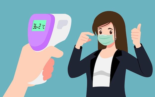 Uma mão segurando um termômetro infravermelho digital que verifica a temperatura corporal para provar que um empresário que usa máscara está seguro em público. distanciamento social para pessoas seguras de coronavírus, covid-19.