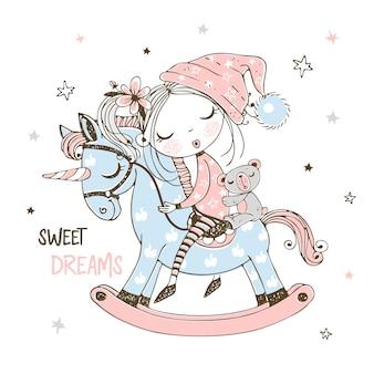 Uma menina bonitinha está dormindo docemente em um cavalo de brinquedo unicórnio.