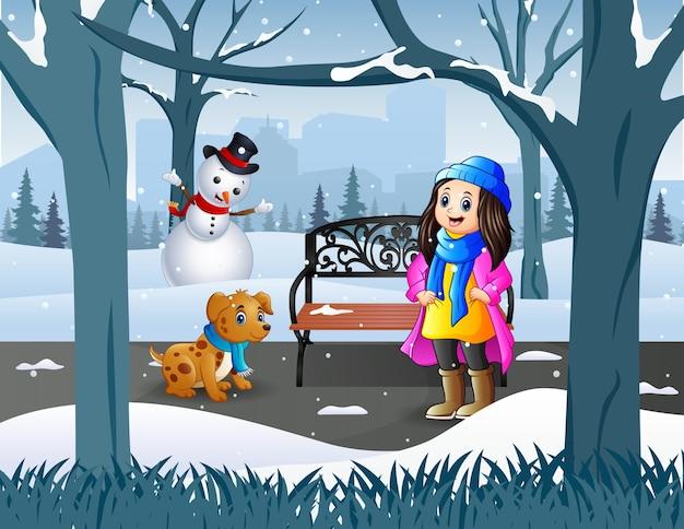 Uma menina com seu animal de estimação caminhando no parque nevado