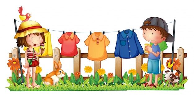 Uma menina e um menino no jardim com as roupas penduradas