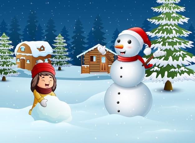 Uma menina fazendo boneco de neve no inverno e paisagem de neve