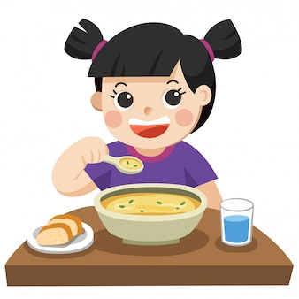 Uma menina feliz em comer sopa.