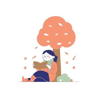 Uma menina lendo um livro debaixo de uma árvore no outono