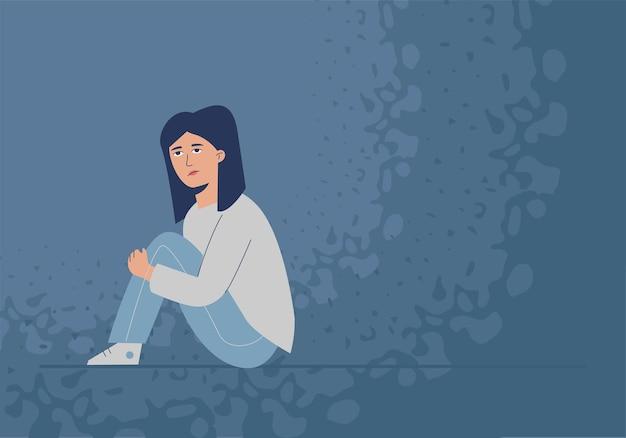 Uma menina triste e reprimida está sentada no chão.