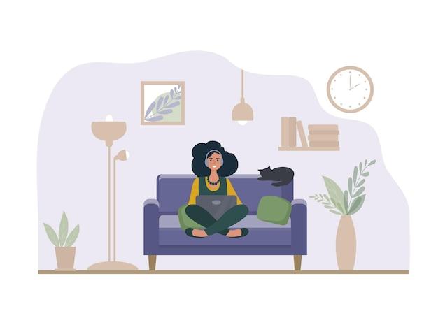 Uma mulher com um laptop sentada no sofá