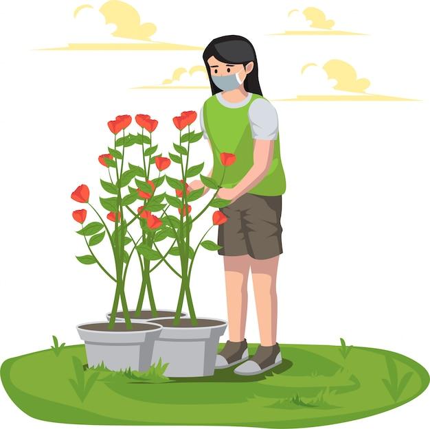 Uma mulher cuidando de suas flores no quintal enquanto usa máscara médica