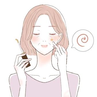 Uma mulher de meia-idade que pinta corretivo no rosto e o mistura com os dedos. sobre um fundo branco.