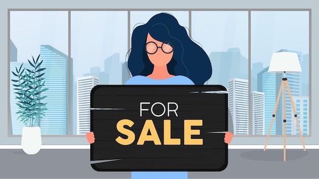 Uma mulher de óculos segura uma placa de madeira com a inscrição à venda. jovem mulher segurando uma placa de madeira. o conceito de vender um apartamento, escritório ou edifício. vetor.