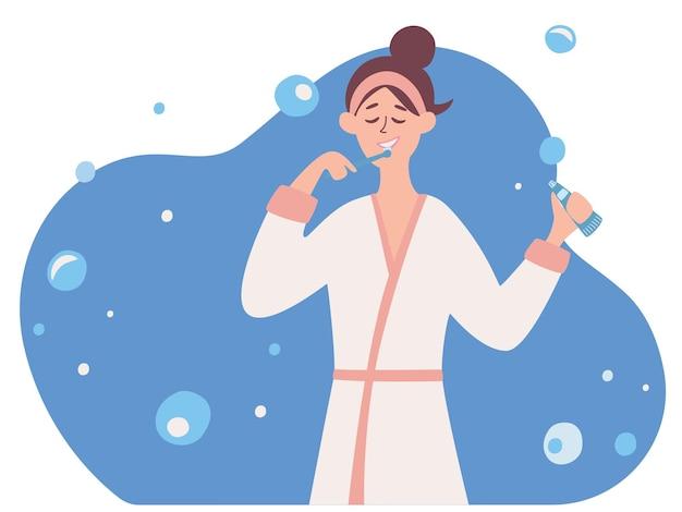 Uma mulher escovando os dentes conceito de atendimento odontológico uma menina de roupão escova os dentes