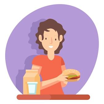 Uma mulher está comendo um hambúrguer na hora do almoço em uma cantina da empresa