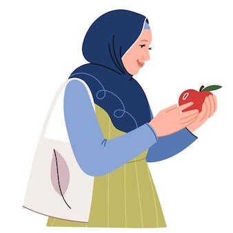 Uma mulher muçulmana moderna em um hijab e com uma sacola ecológica compra frutas