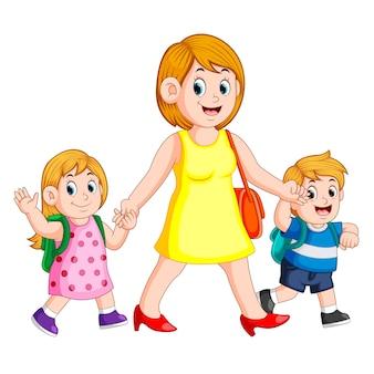 Uma mulher segurando as mãos de seus filhos para acompanhá-los para a escola