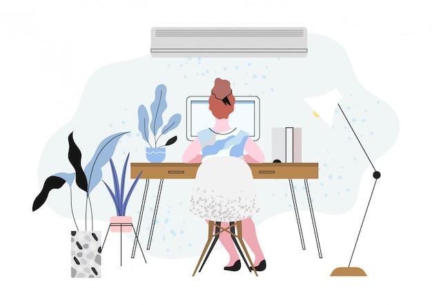 Uma mulher sentada em uma sala equipada com ar condicionado.