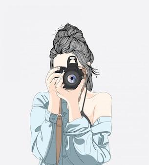 Uma mulher tem uma câmera elegante e veste uma jaqueta jeans