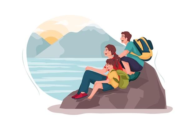 Uma pequena família está assistindo ao pôr do sol na rocha.
