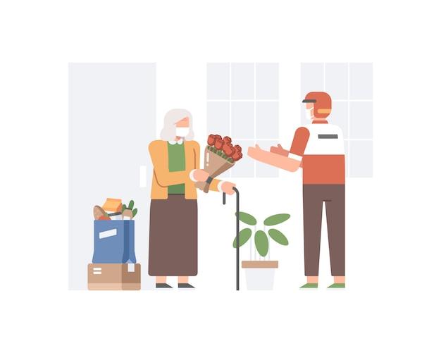 Uma senhora idosa dá um buquê de flores para um entregador que entrega uma comida em sua casa.