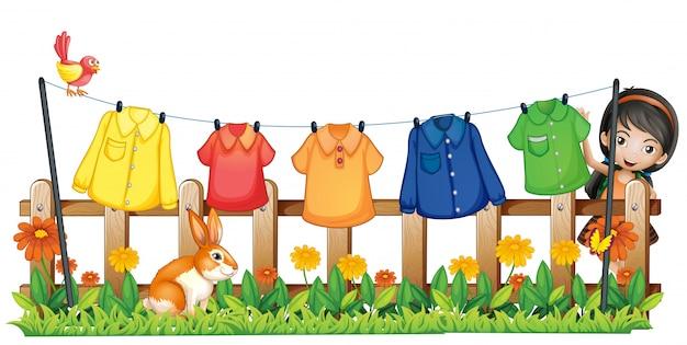 Uma senhora pendurando suas roupas no jardim