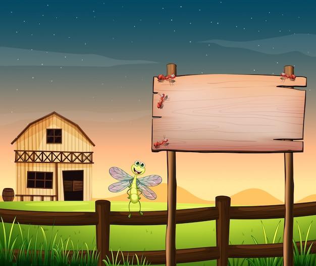 Uma tábua de madeira vazia perto da cerca com uma libélula
