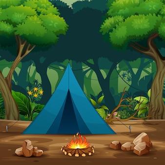 Uma tenda azul com fogueira no fundo da floresta