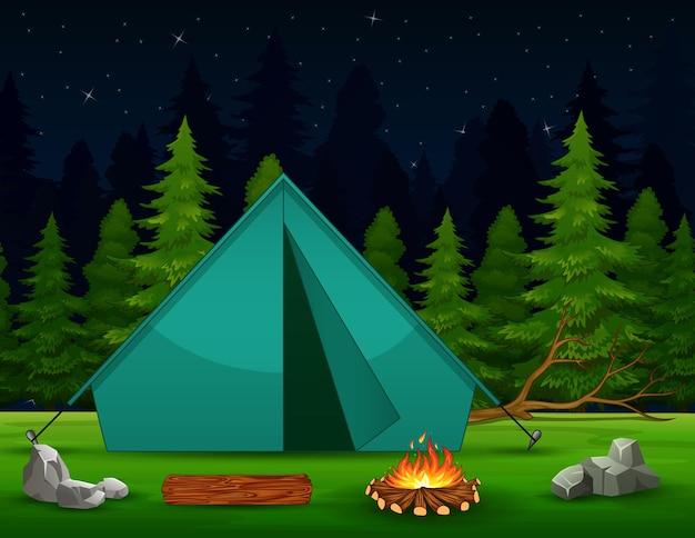 Uma tenda verde com fogueira na paisagem da floresta à noite