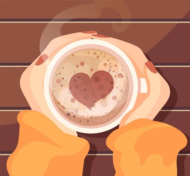 Uma xícara de café quente com um padrão de coração nas mãos das mulheres.