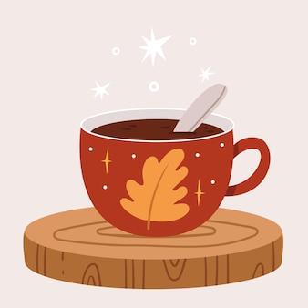 Uma xícara vermelha de outono com uma folha de carvalho fica em um corte de madeira.