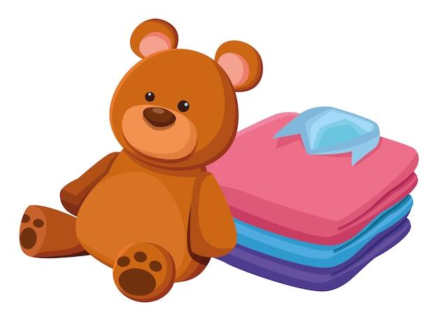 Ursinho de pelúcia brinquedo e roupas dobradas