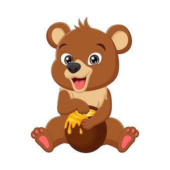 Urso de bebê engraçado de desenho animado sentado e comendo mel do pote
