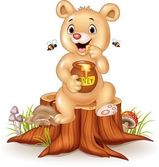 Urso de bebê engraçado dos desenhos animados segurando o pote de mel no toco de árvore