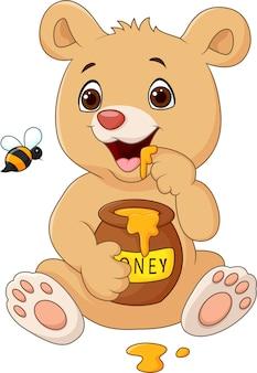 Urso de bebê engraçado dos desenhos animados segurando pote de mel isolado